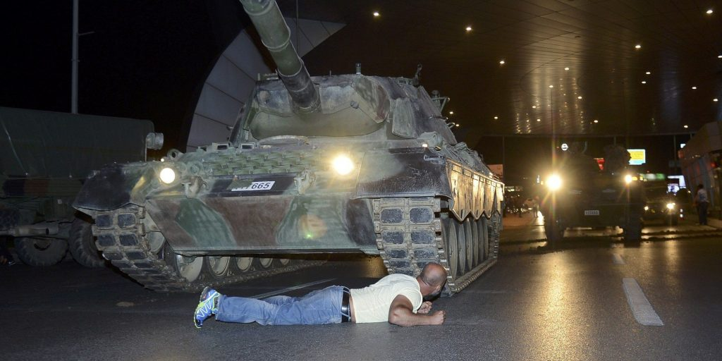 A man lies in front of a Turkish army tank at Ataturk airport in Istanbul, Turkey July 16, 2016. REUTERS/IHLAS News Agency NO SALES. NO ARCHIVES. TURKEY OUT. NO COMMERCIAL OR EDITORIAL SALES IN TURKEY.