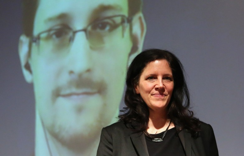 BERLIN, GERMANY - DECEMBER 14: Filmmaker Laura Poitras stands on the stage as former National Security Agency (NSA) contractor turned whistleblower Edward Snowden is seen on a video conference screen during an award ceremony for the Carl von Ossietzky journalism prize on December 14, 2014 in Berlin, Germany. Poitras, Snowden and journalist Glenn Greenwald (the latter two in absentia) were awarded the prize by the International League for Human Rights for having 'put their personal freedom on the line to expose abuse of power' by Germany and the United States in their revelations of the extent of government surveillance on ordinary citizens in the name of 'national security' in the wake of terrorist attacks. The prize is named for journalist and Nobel Peace Prize winner Ossietzky, who died from complications from being held as a dissident in a Nazi concentration camp. A bid to allow Snowden, who has temporary asylum in Moscow, to testify in Berlin before an NSA parliamentary inquiry is ongoing. (Photo by Adam Berry/Getty Images)